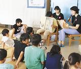 話を聞きながら絵本を見る児童