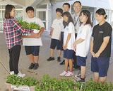 鎌倉市社協の担当者(左)に挿し木を渡す相馬君(左から2人目)と生徒ら