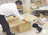 段ボールを組み立てる小学生
