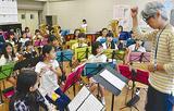 角皆教諭(右)の指揮に合わせて練習する児童