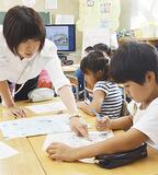 教諭から災害時に取るべき行動を学ぶ児童