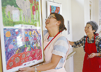 絵を飾る三木さん(左)