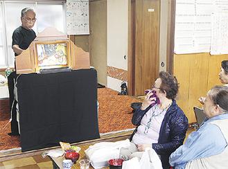紙芝居を演じる今井さん(左上)