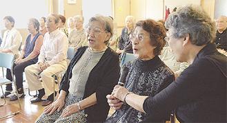 マイクを手に歌う最高齢の吉田さん(右から2人目)