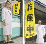 旗を手にする医師会の池田会長(右)と薬剤師会の川田会長