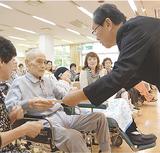 中島区長(右)から記念品を受け取る田中さん