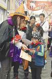 店舗で菓子を受け取る仮装した子ども