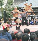 ドロップキックを放つ菊田選手(右)