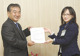 市職員から登録証を受け取る佐々木会長(左)