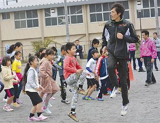 子どもに走り方を指導する苅部さん(右)