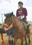 馬に乗り笑顔の親子
