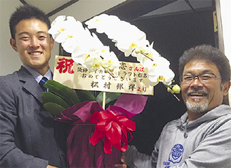 花を持つ望月投手(左)と後藤監督