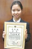 賞状を手に笑顔を見せる川久保さん(学校提供)