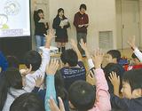 高校生(奥)の問いかけに手を挙げる児童