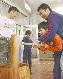 子どもと一緒に餅をつく花村会長(右)