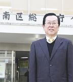 1カ月後に移転する区庁舎の前で今年の展望を語る中島区長