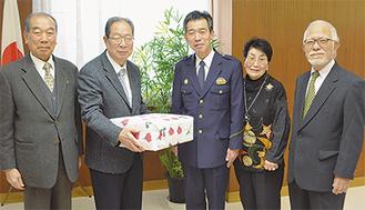 カイロが詰まった贈り物を手渡す中野副会長(左から2人目)