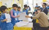 来場者に学援隊の取り組みを説明する児童
