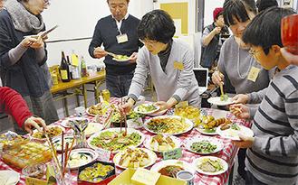 持ち寄った料理を囲む参加者