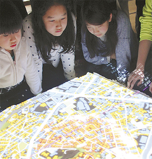 模型に映し出された地図を見る子どもたち