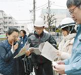 屋外で連絡手段を確認する参加者