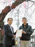 桜まつり実行委員会の水野計委員長(左)から感謝状を受け取る平岡社長