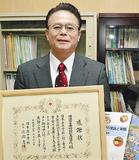感謝状と教科書を持つ福田校長(当時)