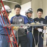 消防団員からロープの結び方を習う参加者