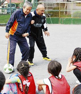 塩澤敏彦さん(左)と次郎さんの指導を聞く児童