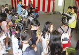空き店舗で音楽演奏を聴く団地住民