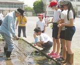 小学生に田植えを指導する会員(同会提供)