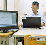 生徒と学習する教室でパソコンを操作する内山教諭