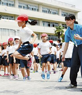 教諭が回す長縄を跳ぶ児童