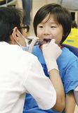 歯科医に口内を診てもらう子ども