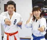 「突き」のポーズをとる有士さん(左)と京子さん