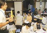 永田町上第三町内会の住民にガイドの内容を説明する区職員(左)