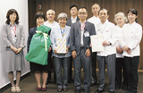 玩具を受け取った濱田理事長(前列左から3人目)、大木節裕区長(同4人目)と洋菓子店主ら