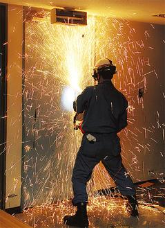 鉄製の扉をエンジンカッターで切断する消防団員