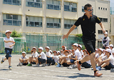 バトンパスの練習をする渡邉さんと児童