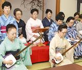 奥村会長(前列右)の三味線に合わせ歌う出演者