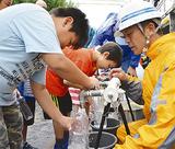 給水車の水をペットボトル入れる子ども