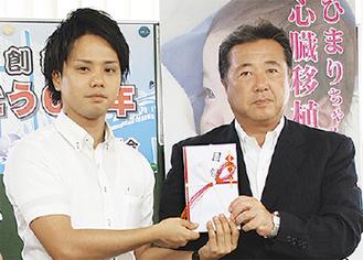 飯島組合長(右)から目録を受け取る上原代表