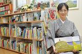笑顔で本を持つ松本さん