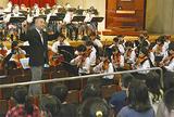 オーケストラ部の演奏に合わせて歌う児童