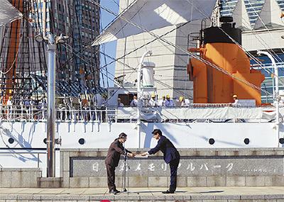 帆船日本丸の前で感謝状を受け取る山本社長(右)