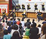 沖縄民謡太鼓を使って演奏する4年生