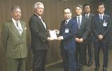 土志田会長(中央左)が大木区長(同右)に目録を渡した
