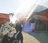 本堂に放水する消防団員ら(南消防署提供)