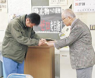 大津会長(右)に寄付金を渡す職員