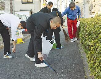 歩道に落ちたごみを拾う生徒